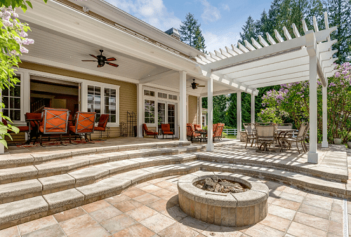 Outdoor deck patio space with white pergola and fire pit