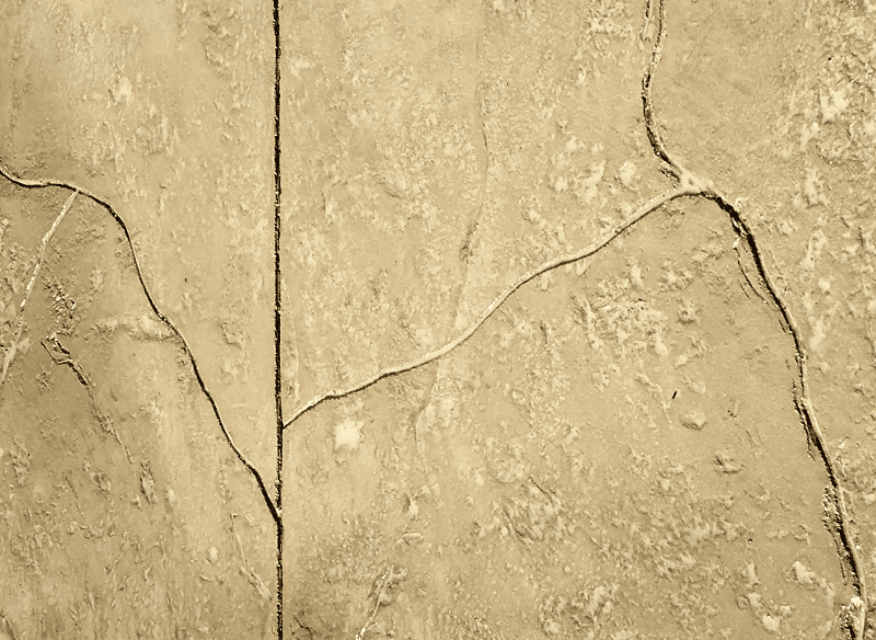 Cream colored stamped concrete with crack
